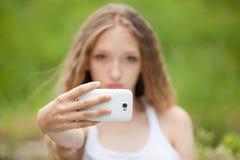 Adolescente femenino hermoso que toma un Selfie con el teléfono Imagen de archivo