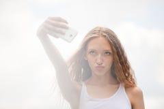 Adolescente femenino hermoso que toma un Selfie con el teléfono Fotos de archivo