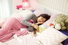Adolescente femenino hispánico enfermo en cama con dolor de cabeza fuerte Imagenes de archivo