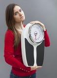 Adolescente femenino infeliz que sostiene una escala del peso con la dimisión Foto de archivo libre de regalías