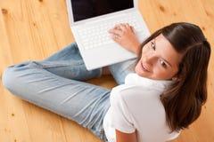 Adolescente femenino joven con la computadora portátil Fotografía de archivo libre de regalías