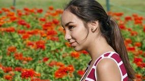 Adolescente femenino joven en jardín de flores Imágenes de archivo libres de regalías
