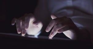 Adolescente femenino joven usando la PC de la tableta en el foco muy bajo oscuro del ambiente Imagen de archivo