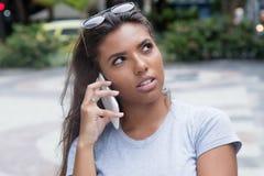 Adolescente femenino latino que escucha en el teléfono elegante Fotografía de archivo