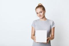 Adolescente femenino lindo con el nudo del pelo, camiseta que lleva, sosteniendo la caja blanca en las manos, preparando la sorpr Fotografía de archivo