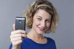 Adolescente femenino lindo que sonríe para el retrato del selfie en el teléfono móvil Fotos de archivo libres de regalías
