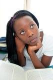 Adolescente femenino pensativo que lee un libro en el país Imagen de archivo