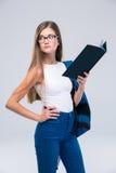 Adolescente femenino pensativo que sostiene el libro y que mira lejos Imagen de archivo