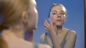 Adolescente femenino que aplica la crema de cara, tratamiento del acné, reflexión de espejo del cuidado de piel almacen de video