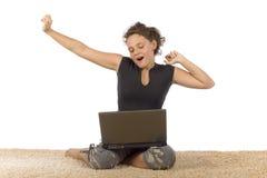 Adolescente femenino que bosteza en la alfombra con la computadora portátil Fotos de archivo