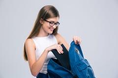 Adolescente femenino que busca algo en mochila Fotografía de archivo
