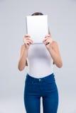 Adolescente femenino que cubre su cara con la tableta Imagenes de archivo