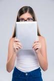 Adolescente femenino que cubre su cara con la tableta Imagen de archivo libre de regalías