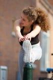 Adolescente femenino que estira ejercicio del músculo de la pierna Fotografía de archivo libre de regalías
