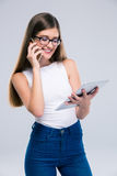Adolescente femenino que habla en el teléfono y que usa la tableta Imagenes de archivo