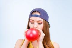 Adolescente femenino que infla el globo rojo Fotos de archivo libres de regalías