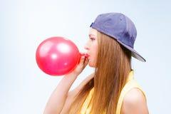 Adolescente femenino que infla el globo rojo Imagen de archivo libre de regalías