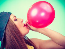 Adolescente femenino que infla el globo rojo Foto de archivo libre de regalías