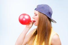 Adolescente femenino que infla el globo rojo Fotografía de archivo