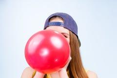 Adolescente femenino que infla el globo rojo Fotos de archivo