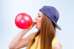 Adolescente femenino que infla el globo rojo Imagenes de archivo