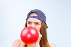 Adolescente femenino que infla el globo rojo Imagen de archivo