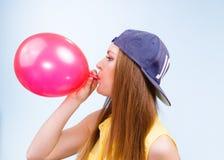 Adolescente femenino que infla el globo rojo Foto de archivo