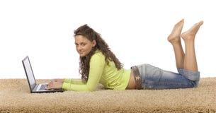 Adolescente femenino que miente en la alfombra con la computadora portátil Imagen de archivo libre de regalías