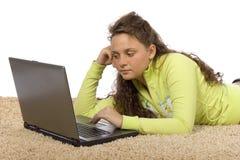 Adolescente femenino que miente en la alfombra con la computadora portátil Imagenes de archivo