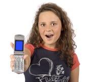 Adolescente femenino que muestra la pantalla de los teléfonos Imagen de archivo libre de regalías