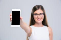Adolescente femenino que muestra la pantalla en blanco del smartphone Imágenes de archivo libres de regalías