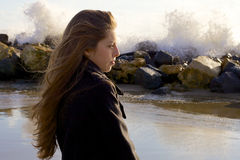 Adolescente femenino que piensa delante de ondas en invierno en la playa Imagen de archivo libre de regalías