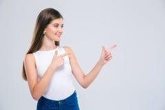 Adolescente femenino que señala los fingeres lejos Foto de archivo