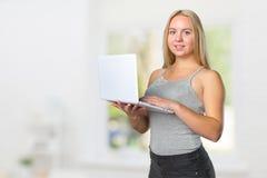 adolescente femenino que se coloca con el ordenador portátil Fotografía de archivo libre de regalías
