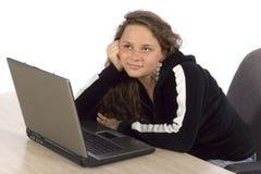 Adolescente femenino que se pregunta en la computadora portátil Imágenes de archivo libres de regalías
