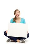 Adolescente femenino que se sienta con el cartel en blanco Foto de archivo