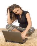 Adolescente femenino que se sienta en la alfombra con la computadora portátil Foto de archivo libre de regalías