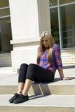 Adolescente femenino que se sienta en pasos de progresión concretos Foto de archivo libre de regalías