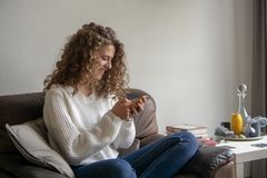 Adolescente femenino que se sienta en una silla que está ocupada con su p digital Imagenes de archivo