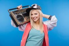 Adolescente femenino que sostiene el equipo estéreo portátil Fotografía de archivo libre de regalías