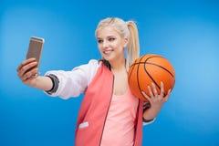 Adolescente femenino que sostiene la bola del baloncesto y que hace la foto del selfie Imagenes de archivo