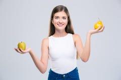 Adolescente femenino que sostiene la manzana y la pera Foto de archivo libre de regalías