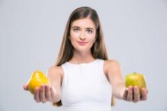 Adolescente femenino que sostiene la manzana y la pera Imagenes de archivo