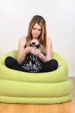 Adolescente femenino que usa el teléfono celular Imagen de archivo libre de regalías