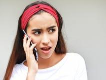 Adolescente femenino que usa el teléfono celular e infeliz hermosos Foto de archivo libre de regalías