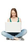 Adolescente femenino que usa la computadora portátil Imagenes de archivo