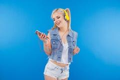 Adolescente femenino que usa smartphone con las auriculares Fotografía de archivo