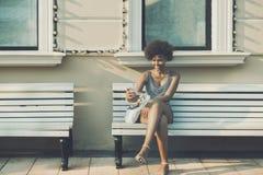 Adolescente femenino rizado sonriente Biracial en el banco Fotos de archivo libres de regalías