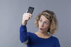 Adolescente femenino rubio que pone mala cara para la imagen del selfie en el teléfono móvil Fotografía de archivo