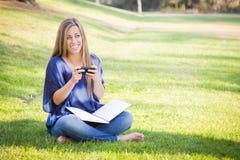 Adolescente femenino sonriente con el libro y el teléfono celular al aire libre Imágenes de archivo libres de regalías